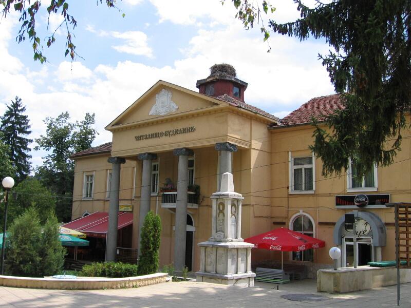 """Сградата на читалище """"Будилник"""" с паметника на загиналите във войните ракитовци (на преден план)"""